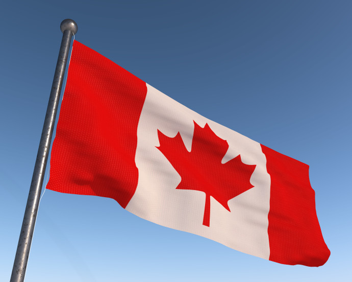 Canada national flag with blue sky in the background.