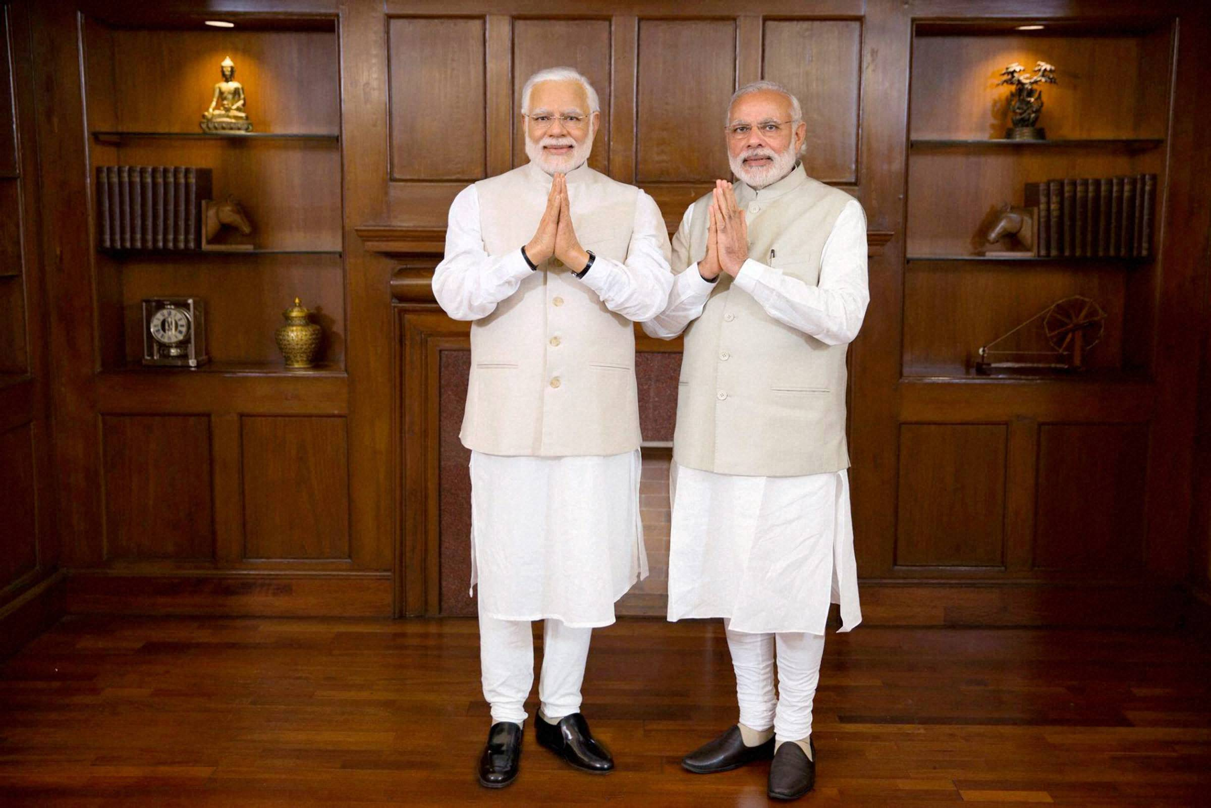 New Delhi: Prime Minster Narendra Modi poses with his wax statue due to be placed at London's Madame Tussauds museum, in New Delhi. Three of his wax statues have been installed in Singapore, Hong Kong and Bangkok and one of them will be put up in London in the next eight days. PTI Photo / Madame Tussauds(PTI4_20_2016_000174B)
