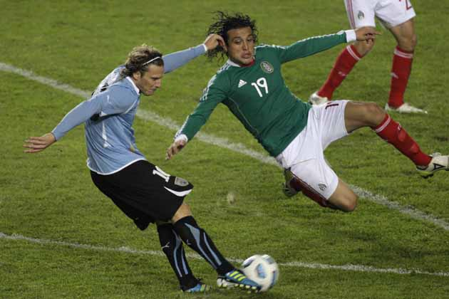 Uruguay's Diego Forlan, left, fights for the ball against Mexico's Hector Reynoso during a Copa America soccer match in La Plata, Argentina, Tuesday, July 12, 2011. (AP Photo/Pedro Fosco)