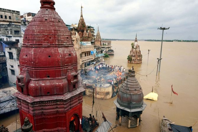 Varanasi: Cremations being performed on the roof a building as the famous Manikarnika Ghat is seen flooded in Varanasi on Monday. PTI Photo (PTI8_22_2016_000289B)