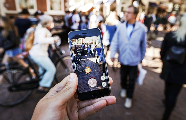 Gamers play with the Pokemon Go application on their mobile phone, at the Grote Markt in Haarlem, on July 13, 2016. / AFP / ANP / Remko de Waal / Netherlands OUT (Photo credit should read REMKO DE WAAL/AFP/Getty Images)