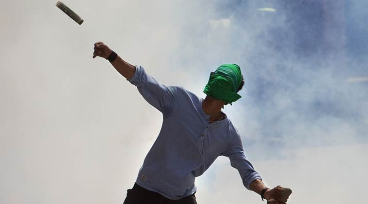 A masked Kashmiri protester throws back an exploded tear gas shell back to Indian policemen during a protest in Srinagar, Indian controlled Kashmir, Friday, June 3, 2016. Anti-India separatist leaders called for protest after Friday prayers against the Indian government's alleged plans to construct separate colonies for Indian soldiers and Hindu Kashmiri Pandit community in the valley. (AP Photo/Dar Yasin)