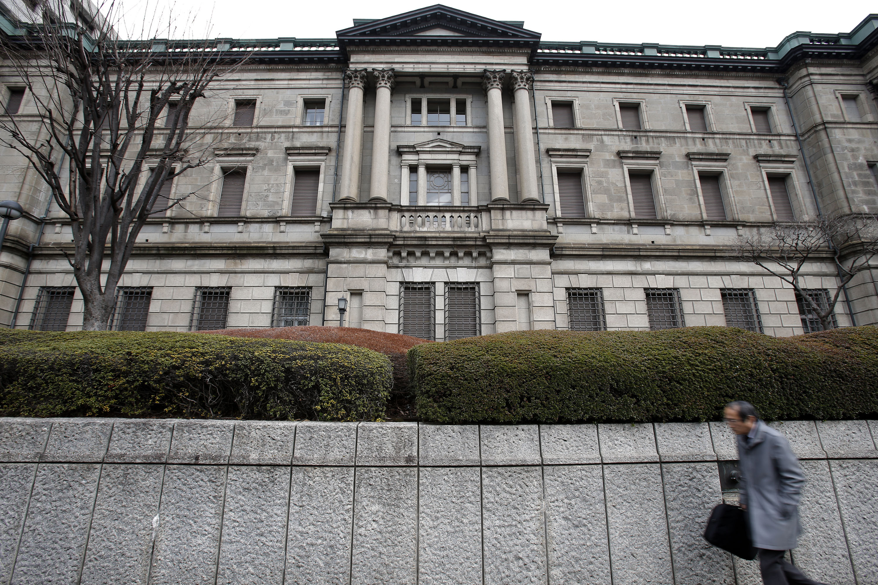 A pedestrian walks past the Bank of Japan headquarters in Tokyo, Japan, on Thursday, Feb. 14, 2013. Asian stocks rose after the Bank of Japan maintained its asset-purchasing program before its governor steps down next month. Photographer: Kiyoshi Ota/Bloomberg