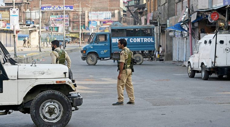Srinagar: Policemen guard a street during restrictions and strike in Srinagar on the fifth consecutive day on Wednesday following the killing of Burhan Muzaffar Wani. PTI Photo by S Irfan (PTI7_13_2016_000084A)