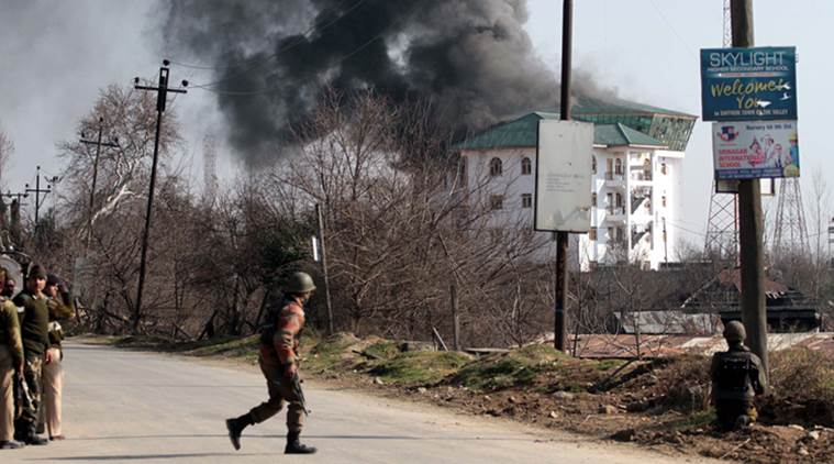 Security personnels looks towards the EDI building that caught fire during an encounter in Pampore outskirts in Srinagar on Sunday. EXPRESS PHOTO BY SHUAIB MASOODI.
