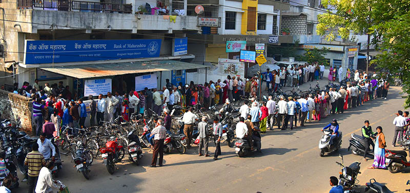 Bank customers waits next to a closed ATM as others queue to exchange old 500 and 1000 rupee notes and deposit money at a bank in Nagpur.India on November 11, 2016. Long queues formed outside banks in India as people crowded into deposit and withdraw money after the two largest denomination notes were taken out of circulation.
