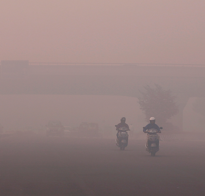 Commuters make their way amidst the heavy smog in New Delhi, India, October 31, 2016. REUTERS/Adnan Abidi - RTX2R4NL